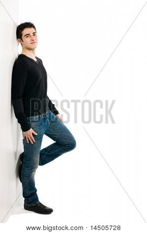 Full length portrait of young smiling man standing against white wall with copy space for your text