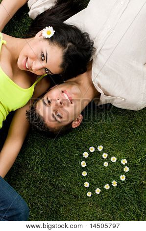 Young couple in love lying in a meadow while looking at camera, heart shape of daisy on the grass.