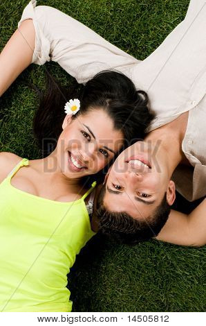 Young couple in love lying in a meadow while looking at camera