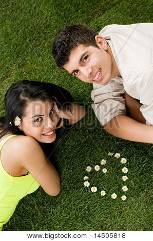 Young couple in love lying in a meadow while looking at camera, heart shape of daisy in the grass