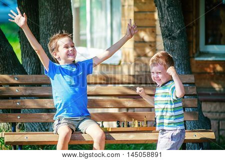 joy and anger after the game of chess. two young players outdoors. the boy is happy that I won a game of chess. the losing opponent is angry, waving their fists and stomping their feet in frustration from losing