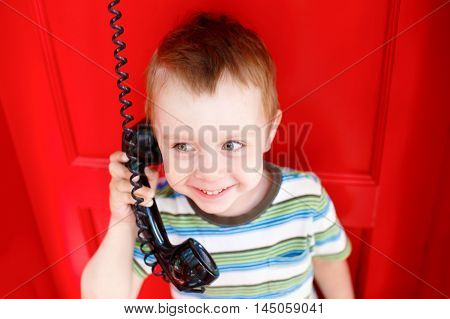 happy kid talking on the phone. little boy stands in a red telephone box and happily smiling in a handset. the concept of family ties and the joy of communion