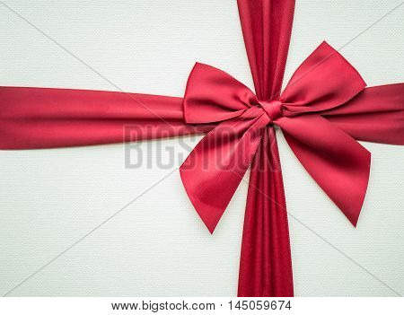 Close up of beautiful red fabric ribbon on wooden paper gift box.