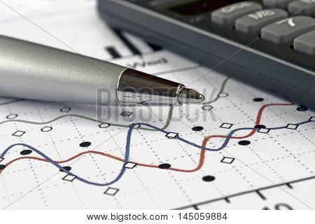 Business background with graph pen and calculator.