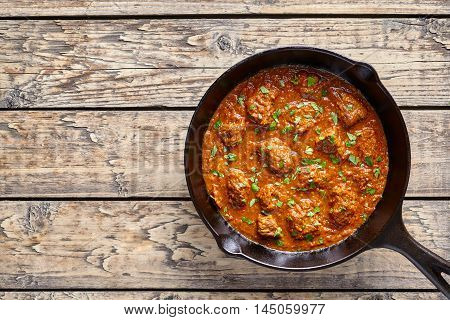Madras butter Beef curry Indian spicy sauce chili lamb meat food with rice garnish and tomatoes in cast iron pan on vintage wooden table background. Traditional India culture restaurant dish.