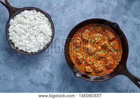 Beef Madras curry slow cook Indian spicy sauce garam masala lamb food in cast iron pan on blue table background. Traditional India culture restaurant dish.