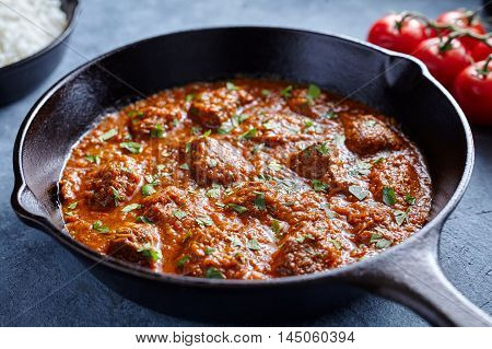 Madras butter Beef spicy slow cook lamb food with tomatoes in cast iron pan on blue table background. Delicious India culture restaurant dish.