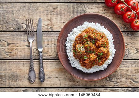 Traditional Madras butter Beef spicy sauce slow cook lamb food with rice and tomatoes in clay dish on vintage wooden table background. Delicious India culture restaurant dish.