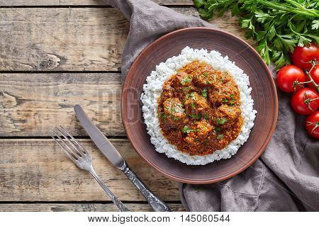 Madras butter Beef spicy Indian masala slow cook lamb and vegetables food with rice and tomatoes in clay plate on vintage wooden table background. Delicious India culture restaurant dish.
