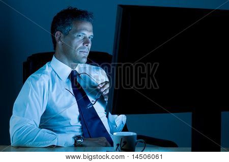 Mature businessman working late at night in his office
