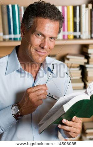 Mature man reading a book with glasses in a library. Looking at camera with confidence.