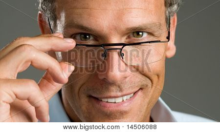 Handsome mature man putting on a pair of modern glasses