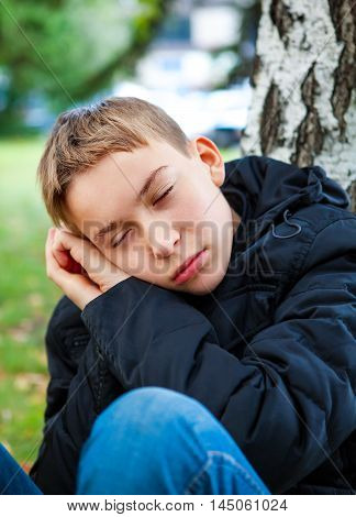 Tired Teenager sleep under Tree in the Park