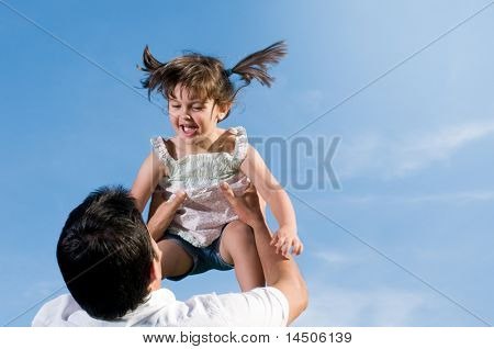 Father throw in air his little daughter in a clear blue sky with copy space for your text