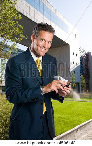 Mature successful businessman text messaging on mobile outdoor in a business park