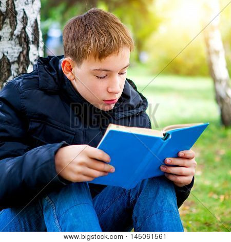Teenager read the Book in the Autumn Park