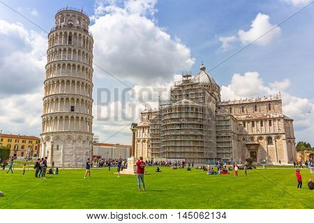 PISA, ITALY - APRIL 11, 2015: Cathedral and the Leaning Tower of Pisa at sunny day, Italy. Pisa is a city in Tuscany known worldwide for the Leaning Tower, one of the biggest landmark.