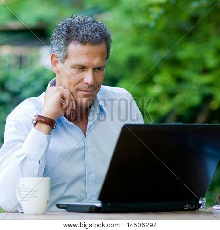 Empresario satisfecho trabajando en el ordenador portátil con conexión inalámbrica a internet