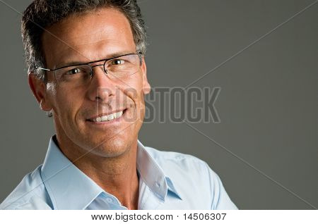 Mature man looking at camera with a bright smile and a pair of glasses. Space for text