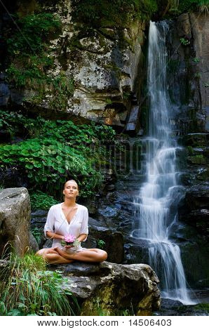 Beautiful young woman meditating and showing a lotus flower while doing yoga in the nature near waterfall
