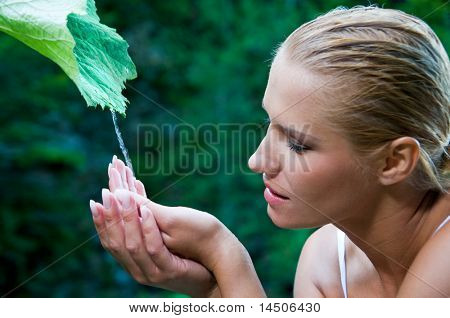 Beautiful young woman with open hands take fresh flowing water from a green leaf in the nature. Symbol of harmony and body care