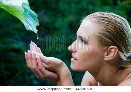Beautiful young woman with open hands take fresh water drops from a green leaf in the nature. Symbol of harmony and body care
