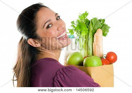Joven sosteniendo una bolsa de supermercado llena de alimentos frescos y saludables, aislado sobre fondo blanco
