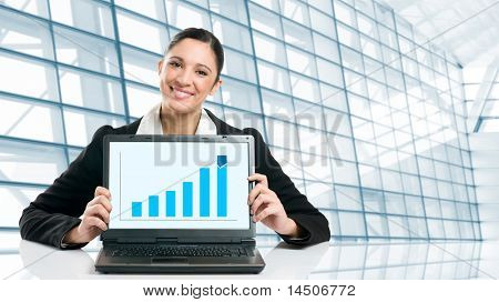 Young business woman displaying successful growing graph on her laptop in a modern office