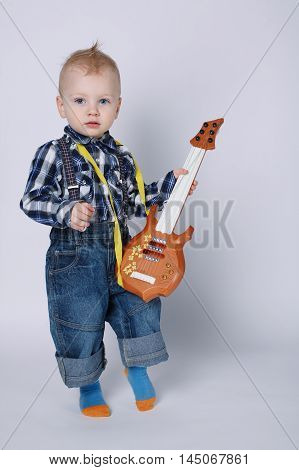 photo of little funny boy with guitar