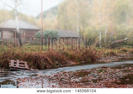 Autumn at mountain village. Morning fog at river