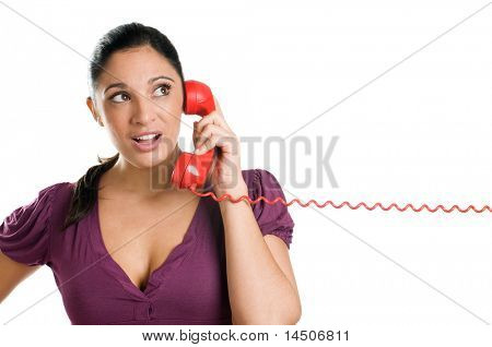 Astonished young casual woman making a call with a red phone isolated on white background