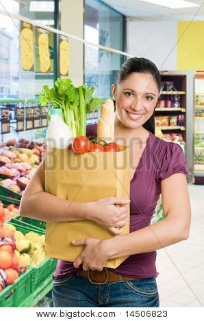Young woman holding a grocery bag full of fresh and healthy food in a supermarket