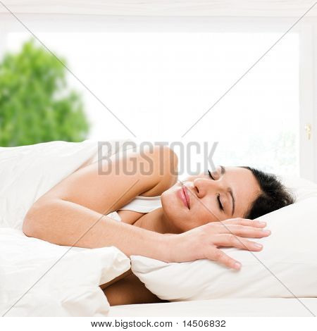 Beautiful young woman sleeping on bed in her bedroom at home in the morning