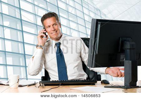 erfolgreicher Geschäftsmann Sit an seinem Schreibtisch beim sprechen auf Mobile in office