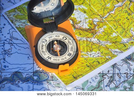 Compass in the black case on an orange ground open the mirror cover is located on a topographic map.
