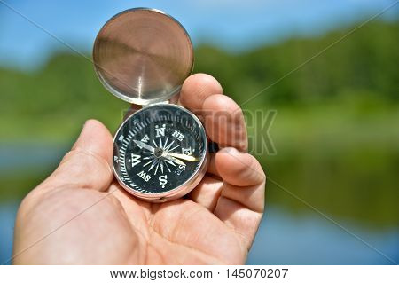Magnetic compass in hand traveler. Tools to guide in the journey.