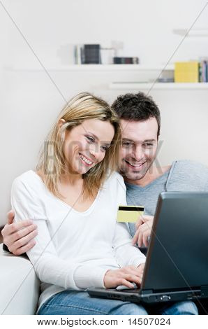 Young couple doing shopping in internet with credit card at home