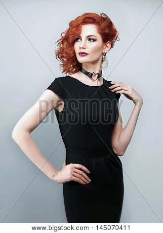 Portrait of beautiful woman with red hair and elegant hairstyle in black dress posing on gray background in studio. Fashion photo.