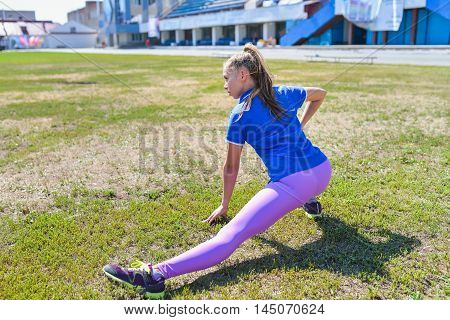 young happy woman doing stretching workout outdoors, back view.