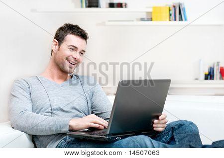Sonriente a joven copia espacio de trabajo en la computadora portátil en casa