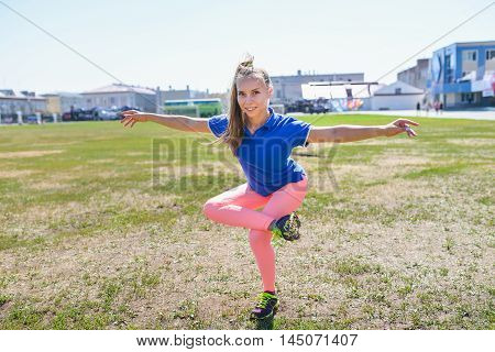 Young beautiful woman doing fitness exercises outdoors.