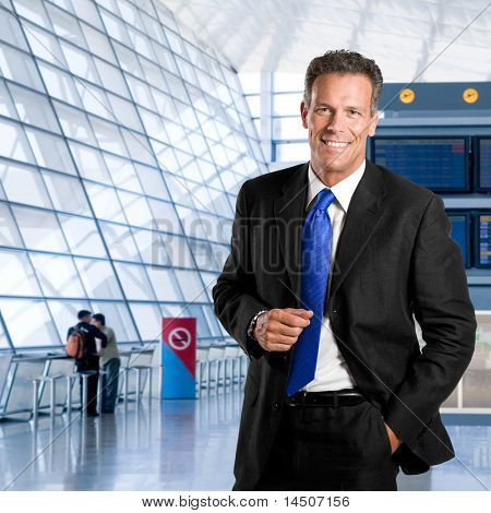Mature successful businessman smiling and looking at camera in a modern airport