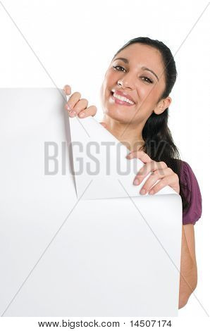 Beautiful smiling young woman looking down on a folded corner of a blank signboard to write it on whatever you want!