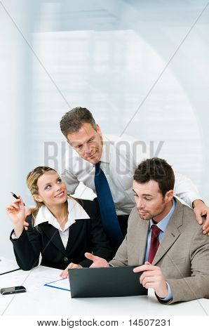 Business colleagues working together during a meeting with mature manager supervising