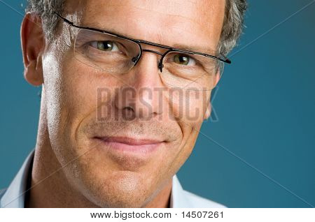 Satisfied mature man with glasses looking at camera smiling