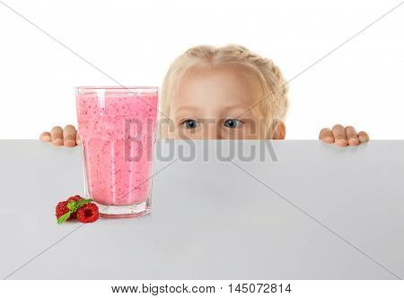 Funny little girl hiding behind white table and looking glass of fresh cold raspberry smoothie