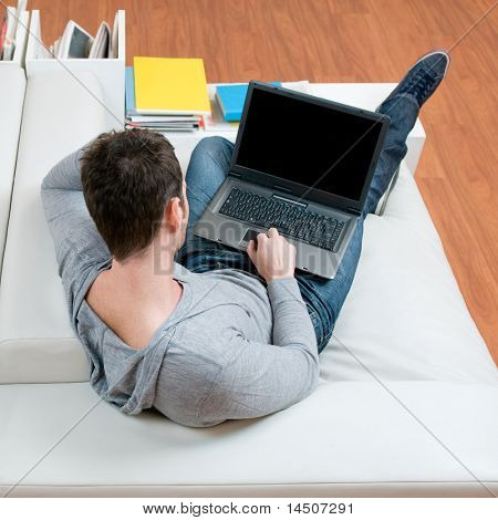 Young casual man working on laptop while lying on the couch in his living room at home, high angle view