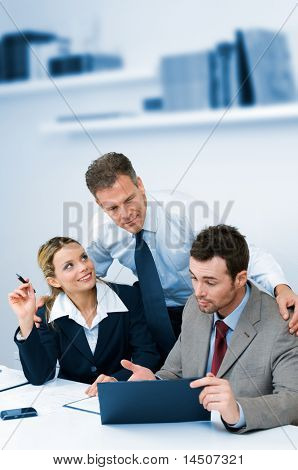 Satisfied mature manager supervising and collaborate with his business team in modern office