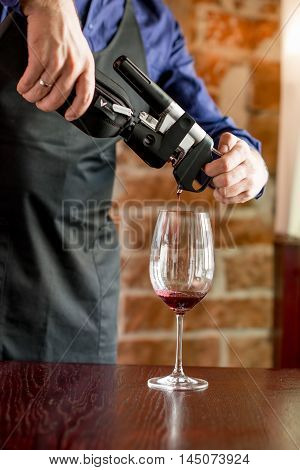 Lviv, Ukraine - August 30, 2016: Sommelier pours wine with Coravin system into the glass. Coravin is patented wine system for pouring wine without taking the cork out of the bottle