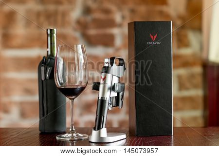 Lviv, Ukraine - August 30, 2016: Coravin wine system with package, bottle and glass on the table. Coravin is patented wine system for pouring wine without taking the cork out of the bottle